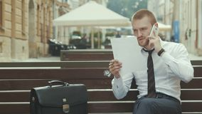 Homem de negócios novo que senta-se no banco que trabalha no acordo e que fala no telefone celular video estoque
