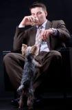 Homem de negócios novo que senta-se no sofá com bebida, dinheiro e um cão Foto de Stock Royalty Free