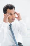 Homem de negócios novo que sofre da dor de cabeça fotografia de stock royalty free
