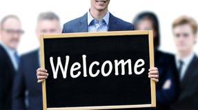 Homem de negócios novo que sustenta um quadro com boa vinda da palavra Fotografia de Stock Royalty Free