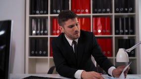 Homem de negócios novo que tem a dor principal durante o trabalho no escritório video estoque