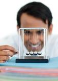 Homem de negócios novo que tem o divertimento com esferas cinéticas Fotografia de Stock
