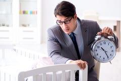 Homem de negócios novo que tenta trabalhar da casa que importa-se após recém-nascido Fotos de Stock Royalty Free