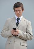 Homem de negócios novo que texting no telefone de pilha Imagem de Stock