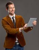 Homem de negócios novo que toca em uma tela da tabuleta. Foto de Stock