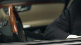 Homem de negócios novo que toca na mobília do salão de beleza luxuoso novo do carro, apreciando a compra filme