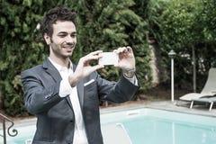 Homem de negócios novo que toma fotos com móbil Imagem de Stock