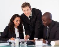 Homem de negócios novo que trabalha com sua equipe Imagem de Stock Royalty Free