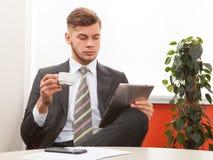 Homem de negócios novo que trabalha com tabuleta Fotografia de Stock