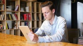 Homem de negócios novo que trabalha com a tabuleta em seu escritório filme