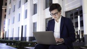 Homem de negócios novo que trabalha com um portátil em um banco dentro na cidade na noite video estoque