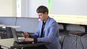 Homem de negócios novo que trabalha no computador e com o telefone em um café video estoque