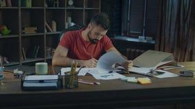 Homem de negócios novo que trabalha no escritório acolhedor Documento no escritório criativo filme