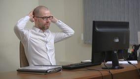 Homem de negócios novo que trabalha no escritório, sentando-se na mesa, olhando o tela de computador