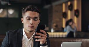 Homem de negócios novo que trabalha no smartphone que senta-se no café acolhedor video estoque