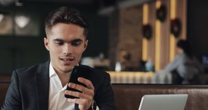 Homem de negócios novo que trabalha no smartphone que senta-se no café acolhedor vídeos de arquivo