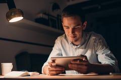 Homem de negócios novo que trabalha usando uma tabuleta tarde na noite fotos de stock