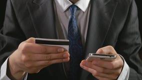 Homem de negócios novo que usa o cartão de crédito da operação bancária em linha em um telefone esperto filme