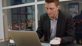 Homem de negócios novo que usa o cartão e o portátil plásticos de banco para a compra em linha video estoque