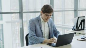 Homem de negócios novo que usa o laptop que recebe a boa mensagem e transformado assento muito entusiasmado e feliz em moderno vídeos de arquivo