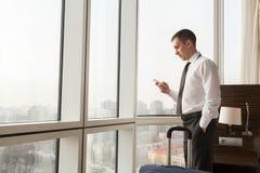 Homem de negócios novo que usa o smartphone na sala de hotel fotografia de stock royalty free