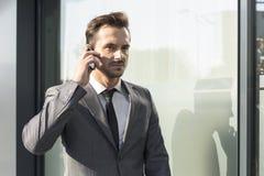 Homem de negócios novo que usa o telefone celular fora do prédio de escritórios foto de stock royalty free