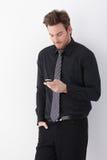 Homem de negócios novo que usa o telefone móvel Fotografia de Stock