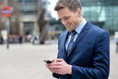 Homem de negócios novo que usa seu telefone celular Fotografia de Stock Royalty Free