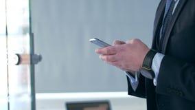 Homem de negócios novo que usa um smartphone video estoque