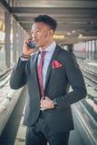 Homem de negócios novo que vai ao aeroporto que fala pelo telefone e foto de stock
