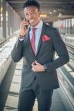 Homem de negócios novo que vai ao aeroporto que fala pelo telefone e fotos de stock