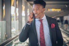 Homem de negócios novo que vai ao aeroporto que fala pelo telefone e foto de stock royalty free
