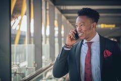 Homem de negócios novo que vai ao aeroporto que fala pelo telefone e imagem de stock