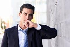 Homem de negócios novo que veste o terno e o laço azuis no fundo urbano Fotografia de Stock