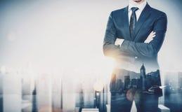 Homem de negócios novo que veste o terno moderno e a posição com seus braços cruzados Exposição dobro Cidade horizontal, contempo foto de stock royalty free