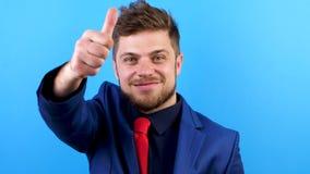 Homem de negócios novo que veste um terno azul e um laço vermelho que mostram os polegares acima filme