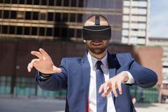 Homem de negócios novo que vestem vidros da realidade virtual e fazer o mais gest Imagem de Stock