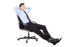 Homem de negócios novo relaxado que senta-se em uma cadeira isolada fotografia de stock