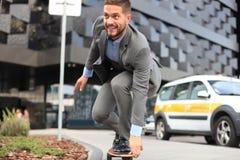 Homem de negócios novo seguro no terno de negócio no longboard que apressa-se a seu escritório, na rua na cidade foto de stock royalty free
