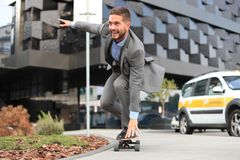 Homem de negócios novo seguro no terno de negócio no longboard que apressa-se a seu escritório, na rua na cidade imagem de stock