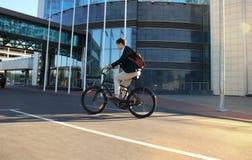 Homem de negócios novo seguro que anda com a bicicleta na rua na cidade foto de stock