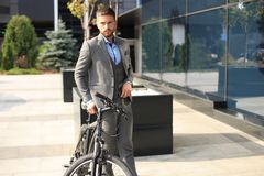 Homem de negócios novo seguro que está com a bicicleta na rua na cidade fotografia de stock