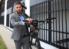 Homem de negócios novo seguro que leva sua bicicleta ao andar fora fotografia de stock royalty free