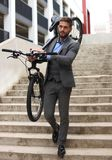 Homem de negócios novo seguro que leva sua bicicleta ao andar fora fotos de stock royalty free
