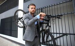 Homem de negócios novo seguro que leva sua bicicleta ao andar fora imagem de stock