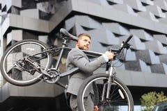 Homem de negócios novo seguro que leva sua bicicleta ao andar fora foto de stock royalty free