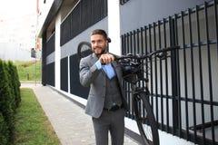 Homem de negócios novo seguro que leva sua bicicleta ao andar fora imagens de stock royalty free