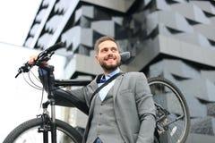 Homem de negócios novo seguro que leva sua bicicleta ao andar fora imagens de stock