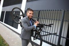 Homem de negócios novo seguro que leva sua bicicleta ao andar fora foto de stock