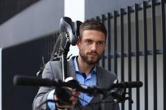 Homem de negócios novo seguro que leva sua bicicleta ao andar fora fotos de stock